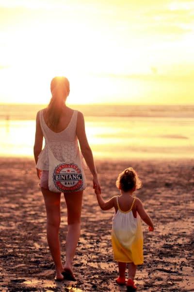 crianza consciente mamá e hija en la playa viendo el atardecer